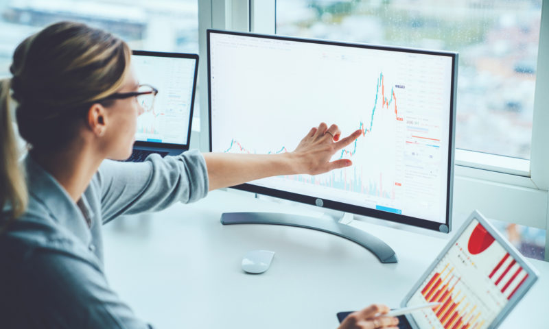 Businesswoman studying graphs on a monitor